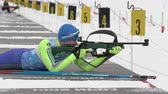 ассортимент : Sportsman biathlete rifle shooting in prone position. Biathlete Napersnikov Nikita in shooting range. Open regional youth biathlon competitions East Cup. Kamchatka Peninsula, Russia - April 12, 2019.