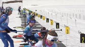 ifjabb : Group of sportswoman biathlete aiming, rifle shooting in prone position on shooting range biathlon stadium. Junior biathlon competitions East Cup. Kamchatka Peninsula, Russian Far East - Apr 13, 2019.