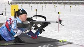 ассортимент : Sportswoman biathlete aiming, rifle shooting prone position. Biathlete Pashitova Karina Saint Petersburg in shooting range. Junior biathlon competitions East of Cup. Kamchatka, Russia - April 13, 2019