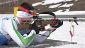 ассортимент : Sportsman biathlete aiming, rifle shooting, reloading rifle in prone position. Biathlete Zlobin Vladislav in shooting range. Junior biathlon competitions East Cup. Kamchatka, Russia - April 13, 2019