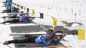 ассортимент : Sportsman biathlete rifle shooting, aiming, reloading rifle in prone position. Biathlete Aleksander Kozulin in shooting range. Junior biathlon competitions East Cup. Kamchatka, Russia - April 13, 2019
