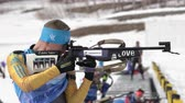 ассортимент : Sportsman biathlete aiming, rifle shooting, reloading standing position. Kazakhstan biathlete Vadim Kurales in shooting range. Junior biathlon competitions East Cup. Kamchatka, Russia - April 13, 2019 Стоковые видеозаписи