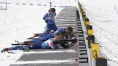 ассортимент : Group of sportsman biathlete aiming, rifle shooting, reloading rifle in prone position during Regional junior biathlon competitions East of Cup. Kamchatka Peninsula, Russian Far East - April 13, 2019.