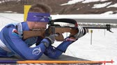 Sportsman biathlete aiming, rifle shooting, reloading rifle in prone position. Biathlete Kozulin Aleksander in shooting range. Junior biathlon competitions East Cup. Kamchatka, Russia - April 13, 2019