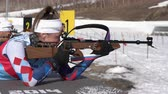 Sportswoman biathlete aiming, rifle shooting prone position. Biathlete Victoria Petrova Saint Petersburg in shooting range. Junior biathlon competitions East of Cup. Kamchatka, Russia - April 14, 2019