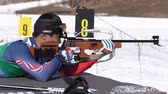Sportsman biathlete aiming, rifle shooting, reloading rifle in prone position. Yang Seon Jik South Korea in shooting range. Junior biathlon competitions East Cup. Kamchatka, Russia - Apr 14, 2019