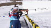 Sportswoman biathlete aiming, rifle shooting standing position. Biathlete Labutina Anna in shooting range. Junior biathlon competitions East Cup. Petropavlovsk City, Kamchatka, Russia - April 14, 2019
