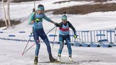 Kazakhstan team sportsman biathletes Kireyev Vladislav and Yegorova Polina skiing snow ski track relay race during Junior biathlon competitions East of Cup. Kamchatka Peninsula, Russia - Apr 14, 2019