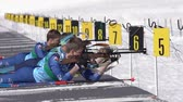 Sportsman biathlete aiming, rifle shooting, reloading rifle in prone position. Biathlete Smolyakov Danila in shooting range. Junior biathlon competitions East of Cup. Kamchatka, Russia - Apr 14, 2019 Stok Video