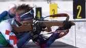 ifjabb : Biathlete aiming, rifle shooting, reloading rifle in prone position. Sportsman biathlete Khmara Yaroslav in shooting range. Junior biathlon competitions East of Cup. Kamchatka, Russia - April 14, 2019