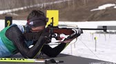 Biathlete aiming, rifle shooting, reloading rifle prone position. Sportsman biathlete Konovalov Vyacheslav in shooting range. Junior biathlon competitions East Cup. Kamchatka, Russia - April 14, 2019