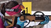 Sportswoman biathlete aiming, rifle shooting in prone position. Biathlete Ivchenko Anastasia in shooting range. Junior biathlon competitions East of Cup. Kamchatka Peninsula, Russia - April 14, 2019