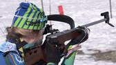 Sportswoman biathlete Legostaeva Anastasia rifle shooting in prone position. Biathlete in shooting range of Junior biathlon competitions East Cup. Kamchatka Peninsula, Russian Far East - Apr 14, 2019.