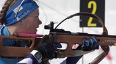アクションショット : Biathlete aiming, rifle shooting prone position. Sportswoman biathlete Ekaterina Galitsyna Saint Petersburg in shooting range. Junior biathlon competitions East Cup. Kamchatka, Russia - Apr 14, 2019 動画素材