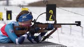 Sportswoman biathlete aiming, rifle shooting prone position. Biathlete Galitsyna Ekaterina Saint Petersburg in shooting range. Junior biathlon competitions East Cup. Kamchatka, Russia - Apr 14, 2019