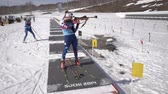 Sportswoman biathlete aiming, rifle shooting in standing position on shooting range stadium. Biathlete Shishkina Vlada. Junior biathlon competitions East of Cup. Kamchatka, Russia - April 14, 2019.
