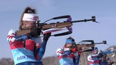 Sportswoman biathlete aiming, rifle shooting, reloading in standing position. Biathlete Petrova Victoria in shooting range. Junior biathlon competitions East of Cup. Kamchatka, Russia - April 14, 2019