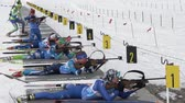 Group sportswoman biathlete aiming, rifle shooting and reloading rifle in prone position. Biathletes shooting range during Junior biathlon competitions East of Cup. Kamchatka, Russia - April 13, 2019.