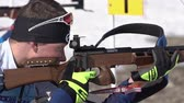 Sportsman biathlete aiming, rifle shooting, reloading rifle in prone position. Biathlete Dionis Roduner in shooting range. Junior biathlon competitions East of Cup. Kamchatka, Russia - April 14, 2019