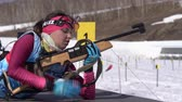 Junior biathlon competitions East Cup. Sportswoman biathlete aiming, rifle shooting in prone position. Biathlete Anastasia Ivchenko in shooting range. Kamchatka Peninsula, Russia - April 14, 2019