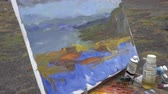 Painter draws brush oil paints on canvas autumn mountains landscape, standing in open air in tundra during overcast weather. Close-up view. Avacha Volcano, Kamchatka Peninsula, Russia - Aug 30, 2019