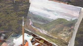 Artist draws brush oil painting on canvas autumn mountains landscape during beautiful gloomy cloudy weather. Avacha Volcano, Kamchatka Peninsula, Russian Far East - August 30, 2019.