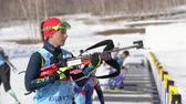 narciarz : Sportswoman biathlete aiming, rifle shooting in standing position. Biathlete Polina Yegorova Kazakhstan in shooting range. Junior biathlon competitions East Cup. Kamchatka, Russia - Apr 14, 2019.