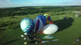 BELGOROD - AUG 5: Balloons fly up in sky with passengers over green field, on Aug 5, 2016 in Belgorod, Russia