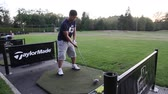 ассортимент : VANCOUVER, BC ,CANADA - CIRCA September 2011 :golf driving range - behind side angle man hits drive