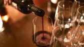 closeup of pouring red wine into many glasses