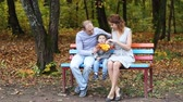 parent : Happy smiling family relaxing in autumn park Stock Footage