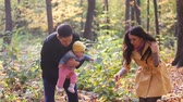 parent : Happy family on walk in park in the autumn small girl Stock Footage