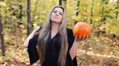 esculpida : beautiful witch with a pumpkin in autumn forest Vídeos