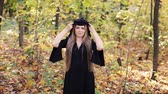 mysterious : young witch in a forest with hood Stock Footage