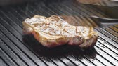 basting : A cook turns up a steak of meat on a grill in slow motion Stock Footage