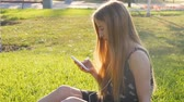 fones de ouvido : Young woman on grass with phone Vídeos