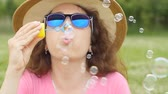 blondehair : Woman blowing soap bubbles at sunset Stock Footage