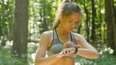 датчик : Young girl athlete practicing fitness outdoors and setting her cardio monitor smartwatch