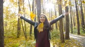 yünlü : Young happy Woman Throwing Autumn Leaves