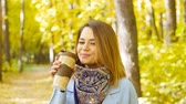 voga : Cute young woman with cup of coffee in the autumn park