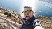 trotteur : Young man taking travel selfie on trekking excursion day. Against the background of the sea and rocks Vidéos Libres De Droits