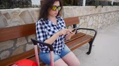 waiting : Young woman traveler sits and looks at smartphone Stock Footage