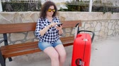 gözcü : Young woman traveler sits and looks at smartphone Stok Video