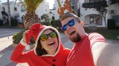 Санта шляпе : Happy couple in santa hats taking selfie picture from hands in summer outdoors
