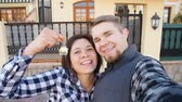 аренда : Young Couple with keys standing outside new home and taking a selfie Стоковые видеозаписи