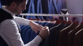 butik : Young man choosing classical suit in the suit shop Stok Video