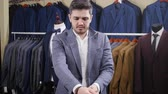 butik : Man puts on a suit in a store Wideo