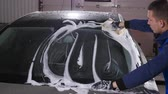 soap water : Man worker washing car with sponge on a car wash station