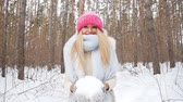 бросать : Young woman throws snow up with a nice smile in the winter forest