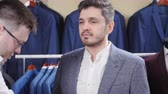 tentar : Man helps another try on a suit in a clothing store Stock Footage